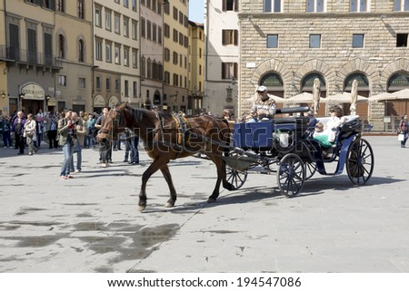 FLORENCE,ITALY-MARCH 31-Tourists visiting the sights on the Piazza San Giovanni and del Duomo.Coachman in the cart carries passengers. March 31,2014  in Florence