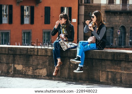FLORENCE, ITALY - MARCH 27, 2014: Two young women eating ice cream sitting on the bridge in the old city center of Florence. - stock photo