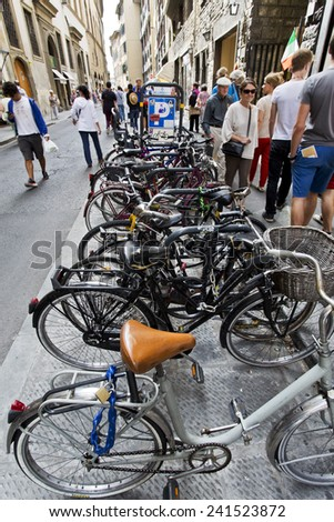 Florence, Italy - September 2014 Bicycles parked on a busy pedestrian street. September 2, 2014 in Florence, Italy. - stock photo