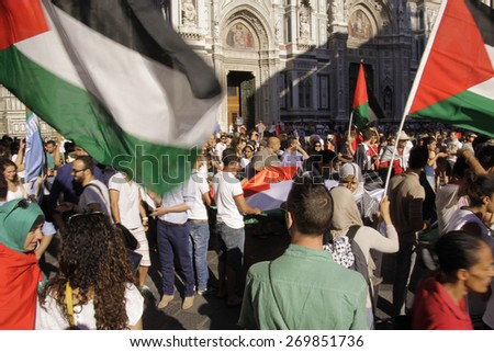 FLORENCE- JUL. 17: Anti-Israeli and Pro-Palestenian demonstrators wave Palestine flags turn up to call for an end to military strikes on Gaza at Piazza del Duomo in Florence, Italy on July 17, 2014.  - stock photo