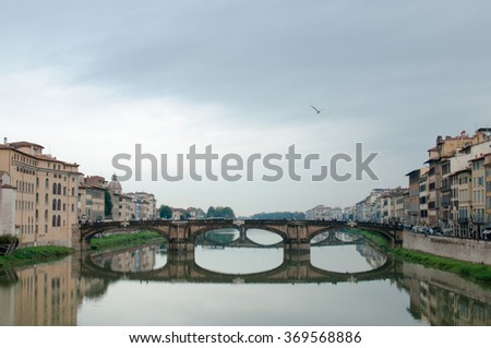 Florence, Ponte alla Carraia medieval Bridge landmark on Arno river, sunset landscape with reflection. Tuscany, Italy. Popular touristic view, travel destination.