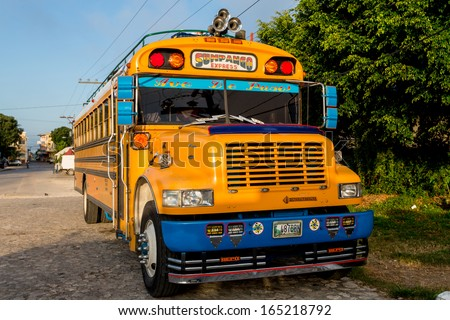 """FLORES, GUATEMALA - NOVEMBER 30: A typical """"Chicken Bus"""" gets ready to go out at dawn in the jungle region of Northern Guatemala, Guatemala - November 30, 2013 - stock photo"""