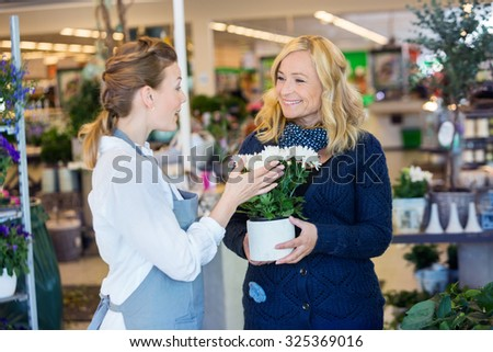 Florist assisting happy female customer in buying flower plants at shop