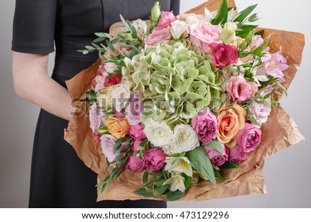 Florist at work. Make hydrangea rich bouquet. Vintage floristic background, colorful roses, antique scissors and a rope on an old wooden table