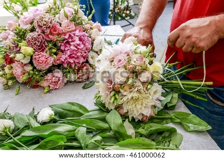 Florist at work: man making a wedding bouquet with dahlias and roses.