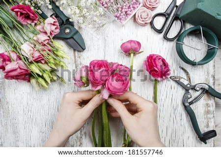 Florist at work. Woman making beautiful bouquet of pink persian buttercup flowers (ranunculus asiaticus)