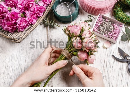 Florist at work: woman making bouquet of pink roses.