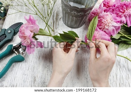 Florist at work. Woman making spring floral decorations of pink peonies