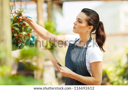 florist checking flowers condition in greenhouse - stock photo