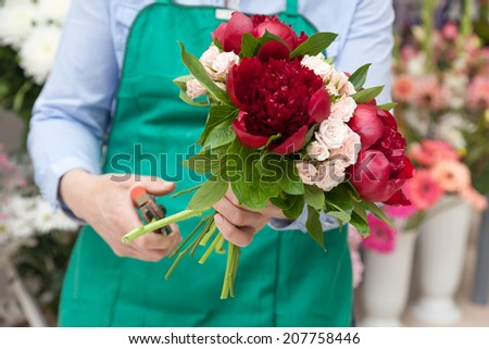 Florist making a red peonies and miniature roses bouquet. Selective focus on flowers. - stock photo