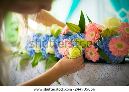 Florist making flower decoration on table