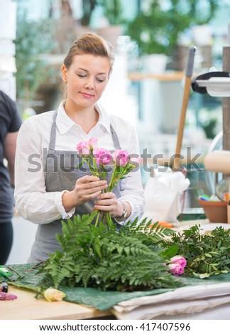 Florist Making Rose Bouquet In Flower Shop - stock photo