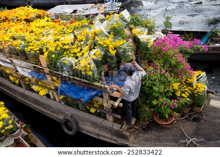 Florist takes care of flowers, prepare for Lunar New Year in Ben Binh Dong flower market, Ho Chi Minh City, Vietnam - stock photo