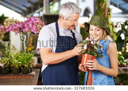 Florist talking to woman with impatiens flower in a nursery - stock photo
