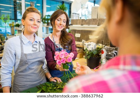 Florists Selling Rose Bouquet To Customer In Shop - stock photo