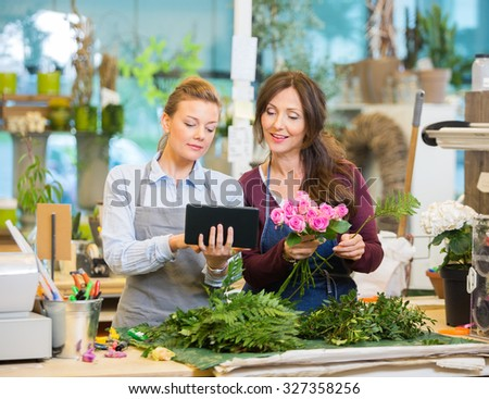 Florists using digital tablet while making bouquet of pink roses in flower shop - stock photo