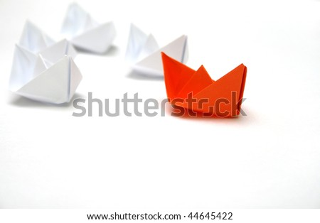 Flotilla of the paper ships led by the red ship. - stock photo