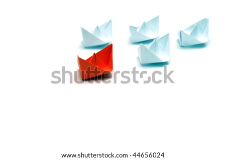 Flotilla of the paper ships led by the red ship - stock photo