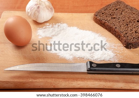 Flour and eggs on a wooden board. The ingredients for making bread - stock photo