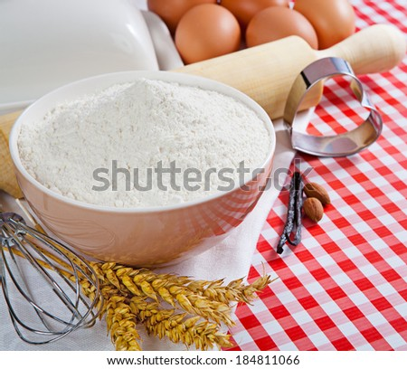 Flour and ingredients for baking in the red checkered tablecloth. Composition with copy space  - stock photo