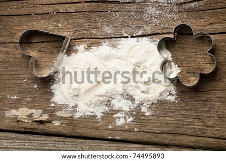 Flour and metal cookie cutter as heart and flower on old wooden table - stock photo