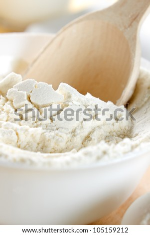 Flour and wooden spoon closeup - stock photo