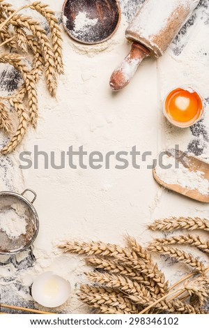 flour baking background with raw egg, rolling pin and wheat ear , top view - stock photo