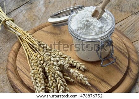 Flour, cereal, wheat and  bread on a wooden table.