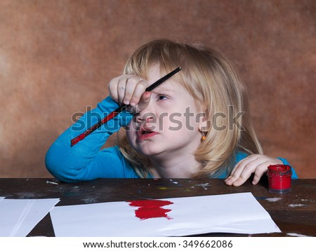 Flour creativity. Small child thinking. The girl thinks that it is necessary to draw. On the table paper and paints. The girl in the hands of the brush. The child draws red. Girl with blond hair