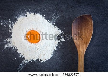 Flour egg yolk and wooden spoon - stock photo