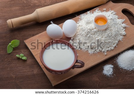 Flour , eggs and milk on dark wooden background. Top view