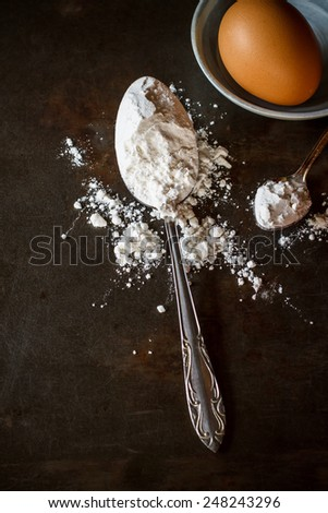 flour for baking in old vintage spoon and egg put on grunge background, image dark tone - stock photo