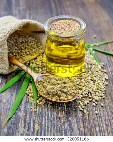 Flour hemp in a wooden spoon, hemp seed in a bag and table, hemp oil in a glass jar, green leaves of hemp on a background of wooden planks - stock photo