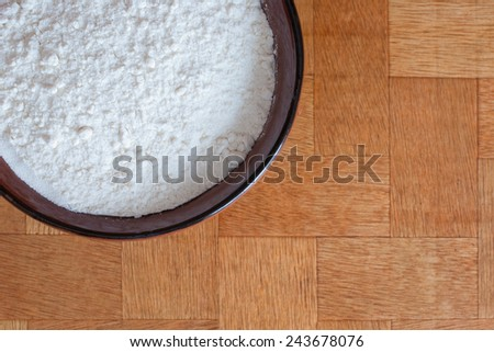 flour in a bowl on wooden background