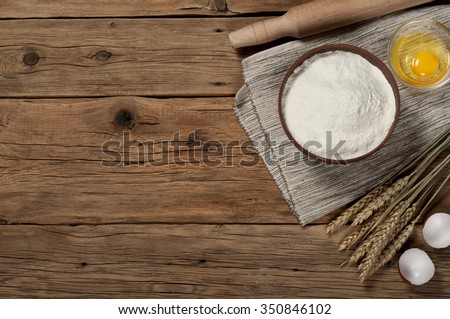 Flour in a bowl with ingredients for preparing baked products. Top view. Copy space. Free space for text - stock photo