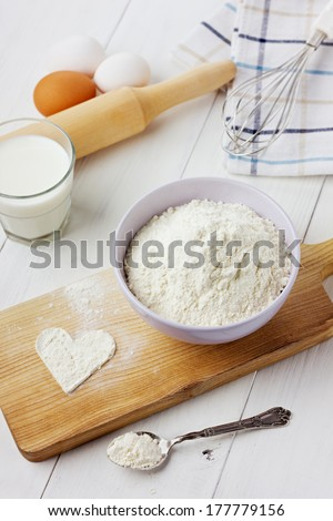 Flour in ceramic bowl with eggs and rolling pin on a white wooden background - stock photo