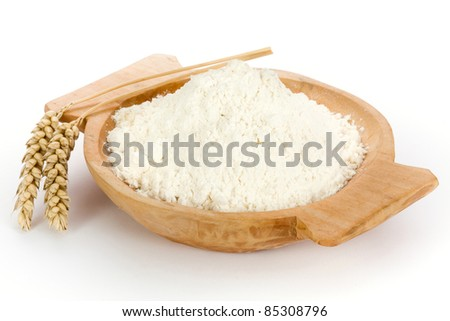 Flour in wooden homemade bowl and wheat ears - stock photo
