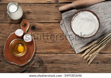 Flour, milk, eggs, in the bakery on a rustic table. Top view with copy space. Baking ingredients - stock photo