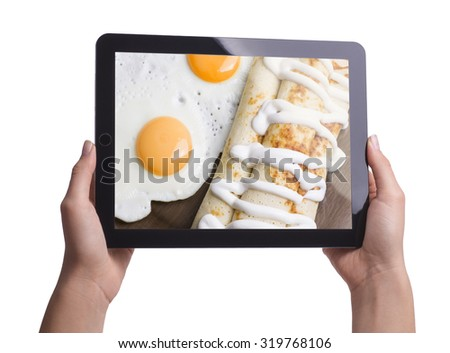 flour pancakes with scrambled eggs on the screen of the tablet - stock photo
