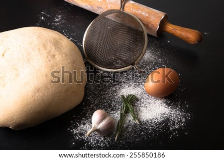 Flour, rolling pin, egg, rosemary, garlic and dough for pie. - stock photo