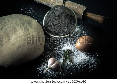 Flour, rolling pin, egg, rosemary, garlic and dough for pie. Toned.