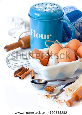 Flour strainer, wooden rolling pin, whisk, measuring spoons and food ingredients for baking on a white. - stock photo