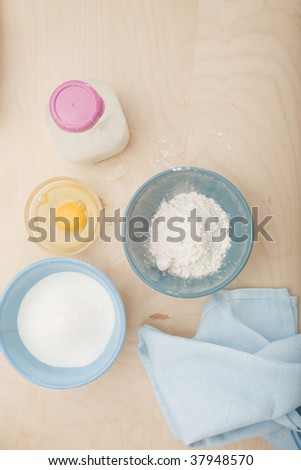 flour sugar and eggs in bowls and a jar of milk - stock photo
