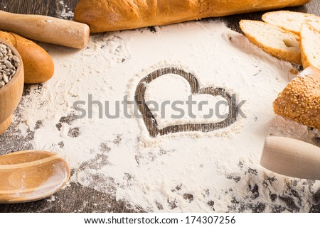 flour with a heart symbol and white bread on a wooden surface - stock photo