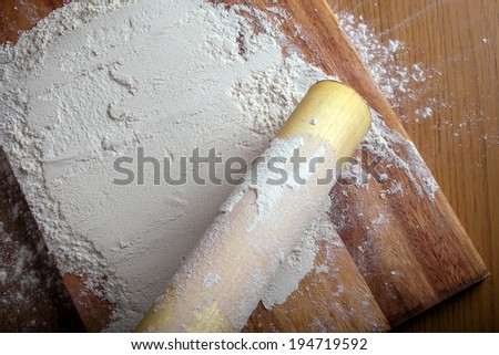 flour with a rolling pin on a cutting board.