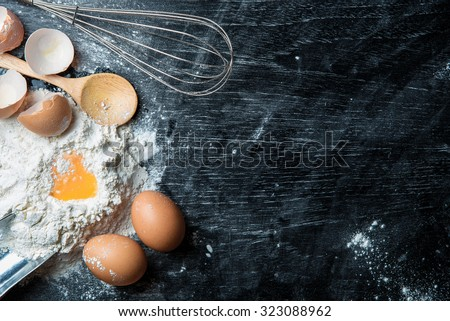flour with egg and ingredients on black table. Top view - stock photo
