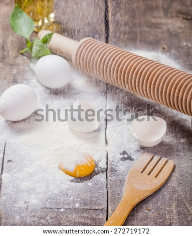 Flour with eggs and rolling pin on wooden table - stock photo