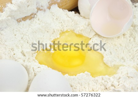Flour with raw eggs and rolling pin for making pastry. - stock photo