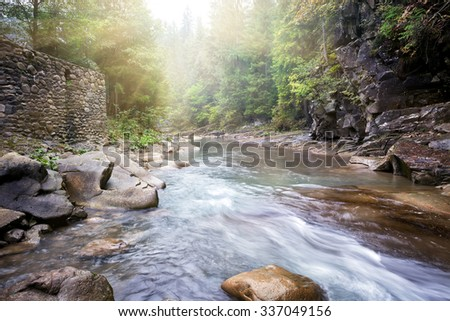 Flow mountain river in rocky shores covered with greenery - stock photo