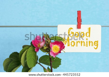 "flower and piece of paper with text ""good morning"" on the wooden table close-up. sunlight effect image"